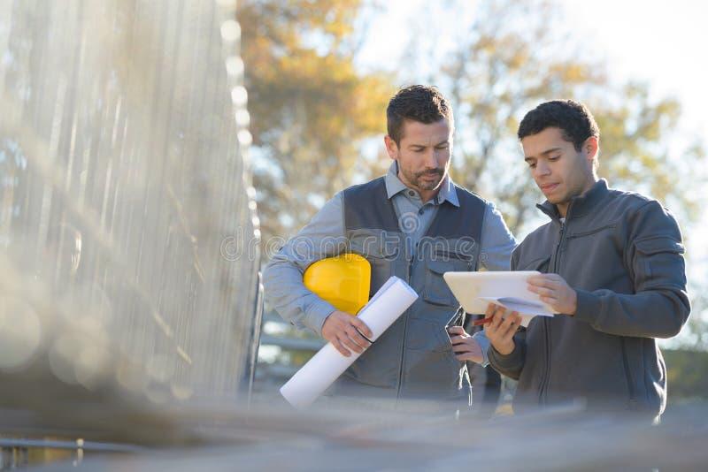 Gerente e trabalhador com o capacete de segurança fora da fábrica foto de stock royalty free