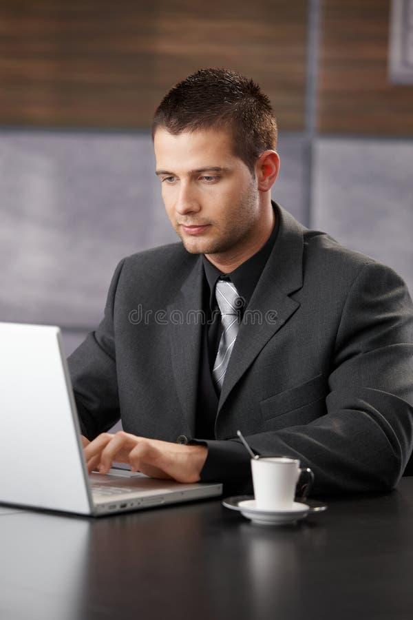 Gerente elegante que trabalha no portátil imagens de stock royalty free