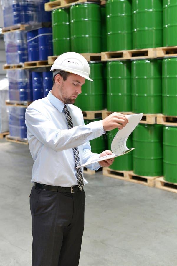 Gerente em um trabalho logístico da empresa em um armazém com produtos químicos fotografia de stock