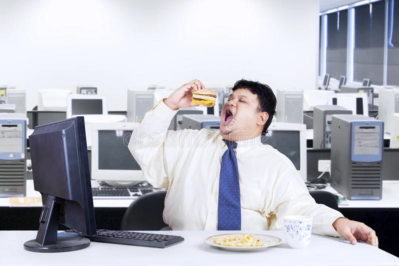 Gerente excesso de peso que come a comida lixo fotografia de stock royalty free