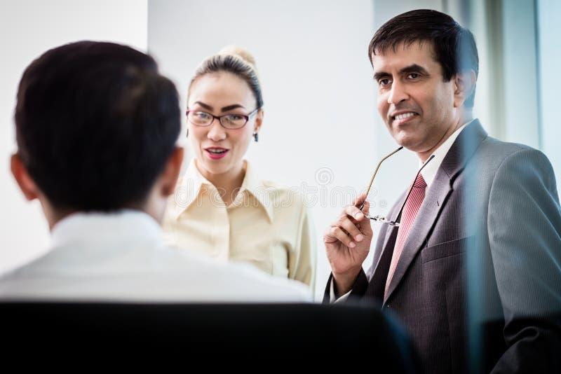 Gerente executivo que fala com os empregados sobre o projeto do negócio foto de stock royalty free