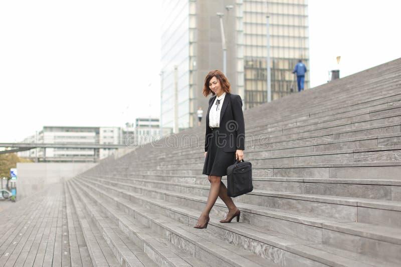 Gerente fêmea americano que vai para baixo em escadas no fundo alto das construções fotografia de stock royalty free