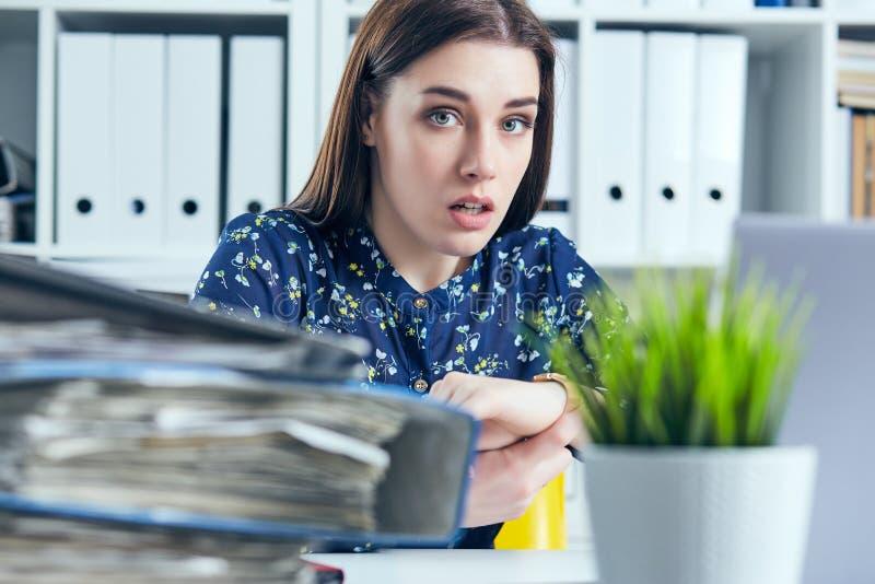 Gerente fêmea chocado que olha seu relógio perto de uma pilha dos originais Conceito do fim do prazo foto de stock