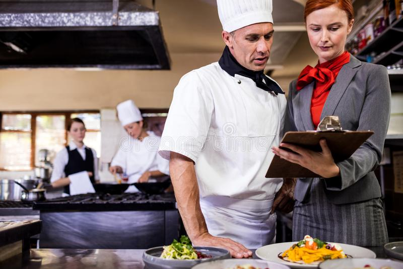 Gerente fêmea e escrita masculina do cozinheiro chefe na prancheta na cozinha imagem de stock royalty free