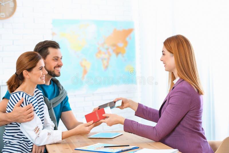 Gerente fêmea que dá passaportes com bilhetes para acoplar-se imagem de stock royalty free