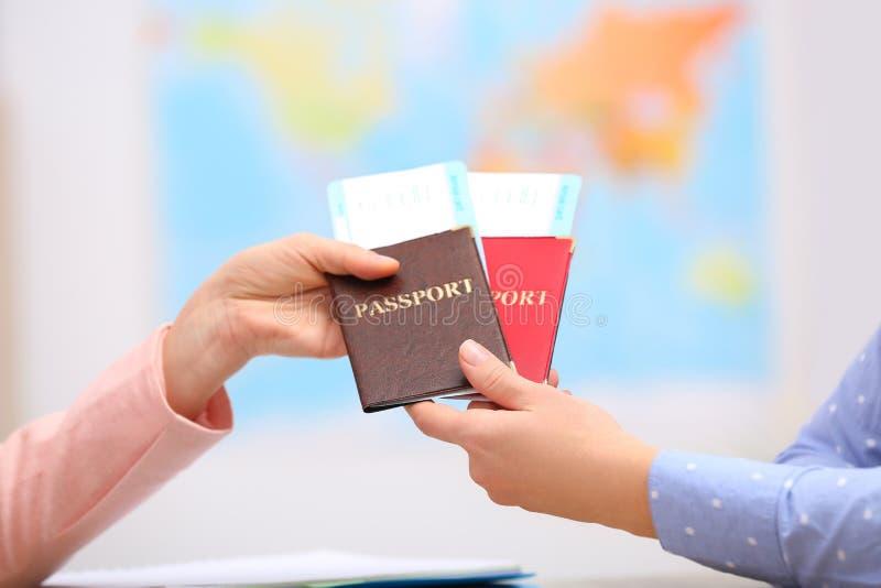 Gerente fêmea que dá passaportes com os bilhetes ao cliente fotos de stock royalty free