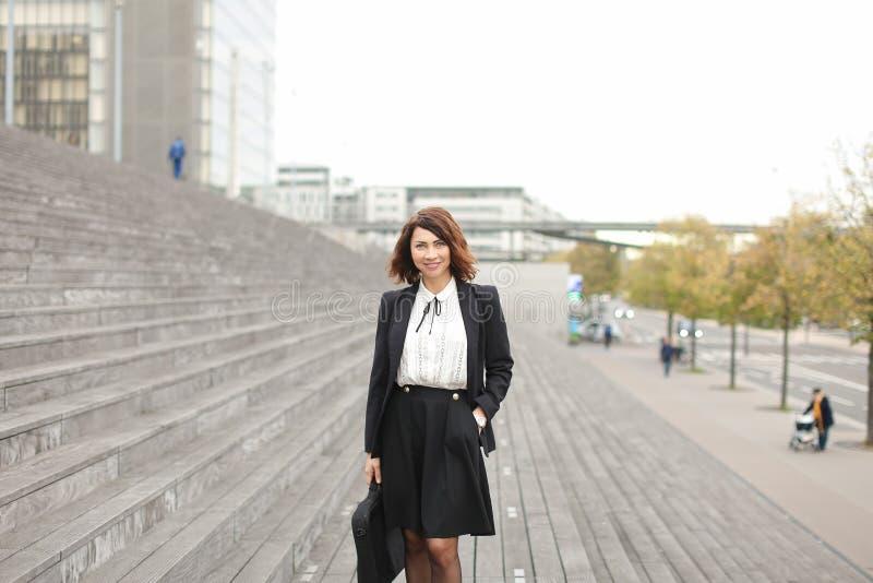 Gerente fêmea que está em escadas fora no fundo alto das construções fotos de stock royalty free