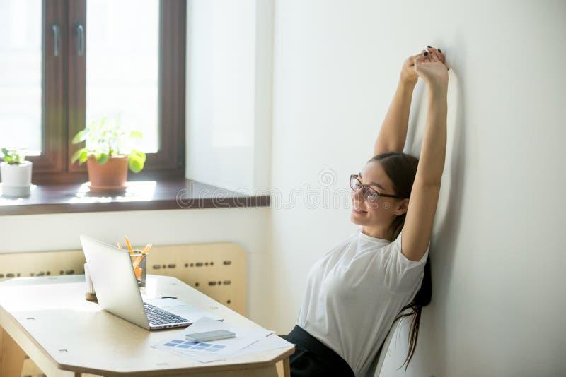 Gerente fêmea que estica acima em sua cadeira imagem de stock royalty free