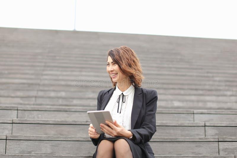 Gerente fêmea que senta-se em escadas com tabuleta e trabalho foto de stock