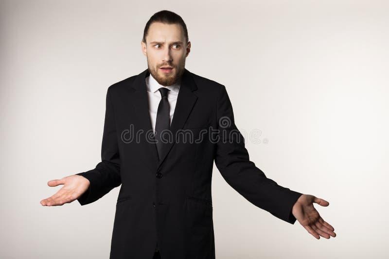 Gerente farpado elegante no terno preto que faz eu não conheço a reação, no fundo branco imagens de stock