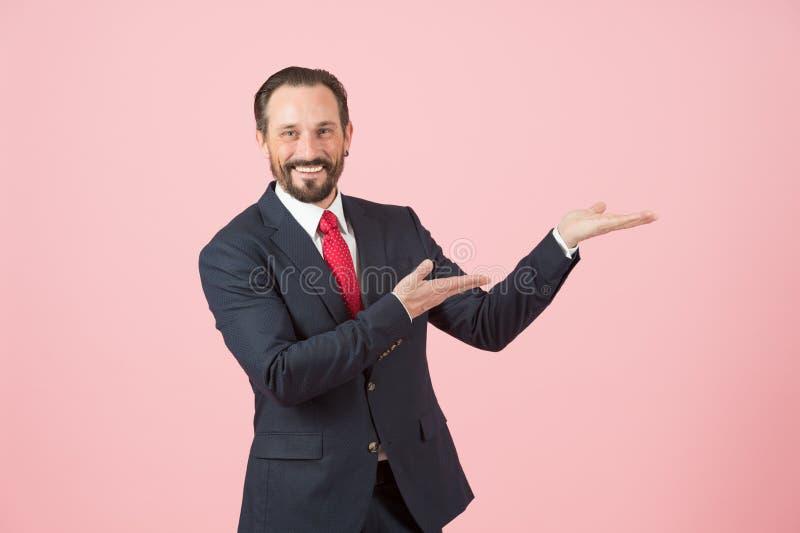 Gerente feliz que mostra por considerável no fundo cor-de-rosa Homem de negócios no terno azul e laço vermelho com sorriso fotos de stock