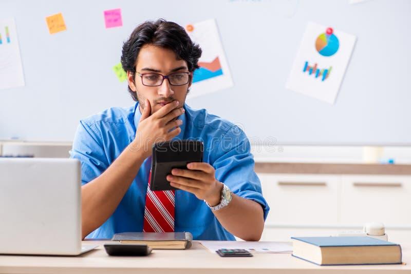Gerente financeiro masculino novo que trabalha no escrit?rio imagens de stock royalty free
