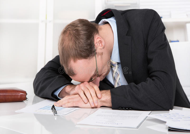 Gerente frustrante com crise que dorme na mesa. foto de stock