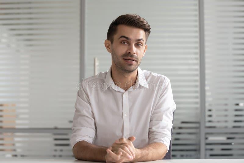 Gerente masculino concentrado sostiene entrevista de trabajo en video distante imágenes de archivo libres de regalías