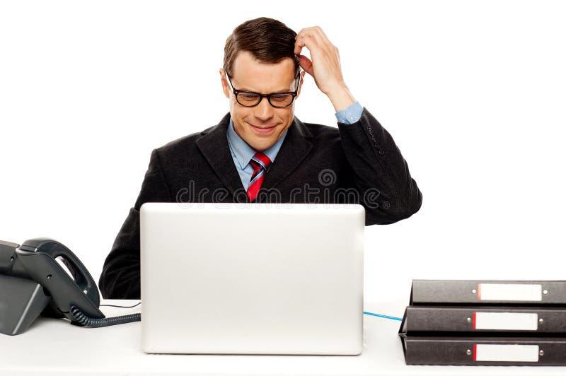 Gerente masculino confuso que itching sua cabeça foto de stock