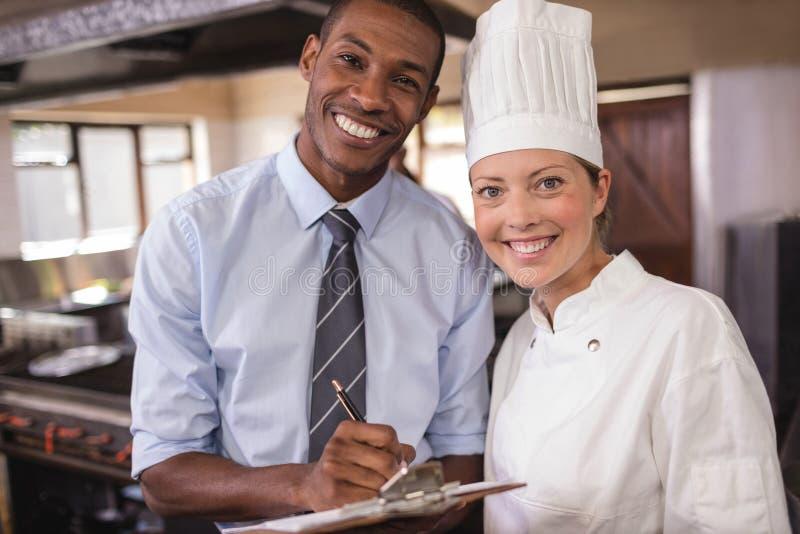 Gerente masculino e escrita fêmea do cozinheiro chefe na prancheta na cozinha imagem de stock royalty free