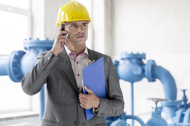 Gerente masculino novo com prancheta usando o telefone celular na indústria foto de stock royalty free
