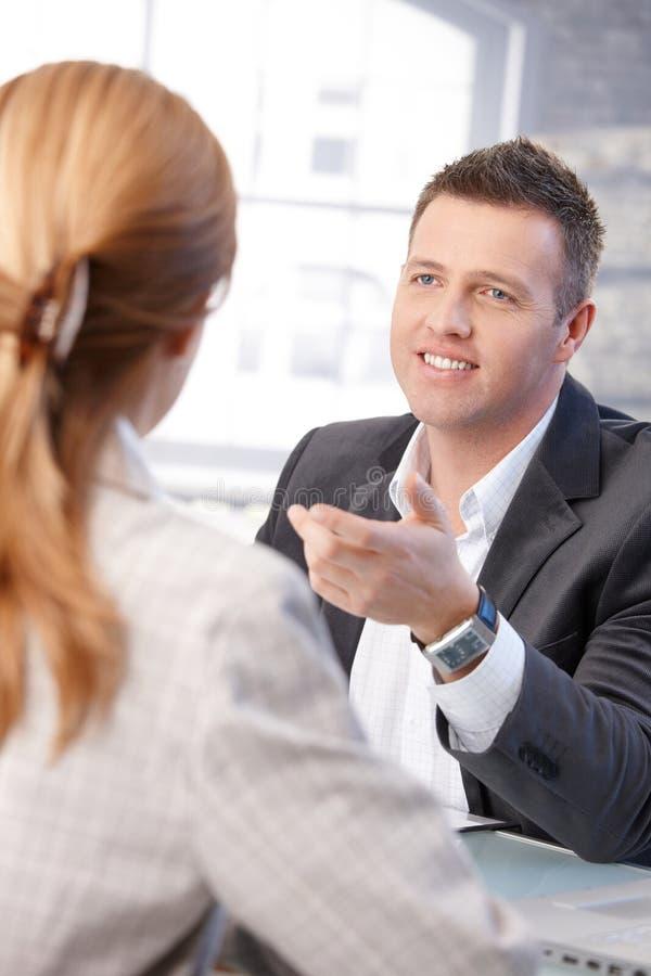 Gerente masculino que entrevista o sorriso fêmea do candidato imagens de stock royalty free