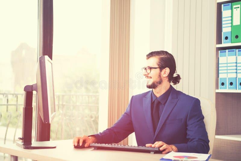 Gerente no terno que trabalha em seu computador ao lado de uma janela de vidro imagens de stock royalty free