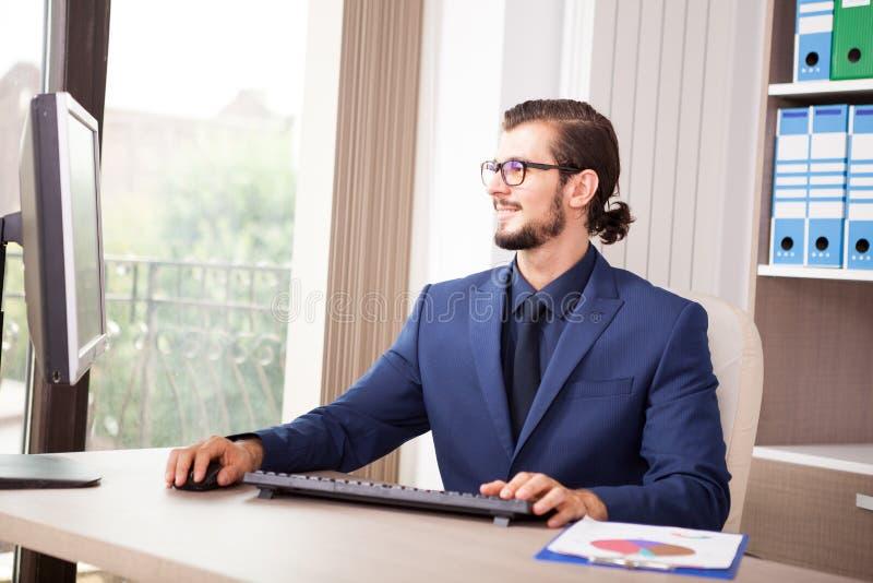 Gerente no terno que trabalha em seu computador ao lado de uma janela de vidro fotos de stock