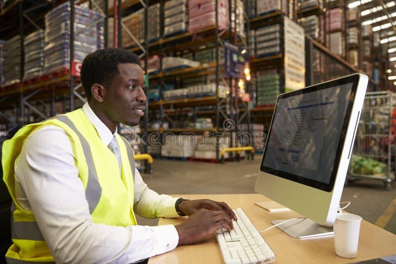 Gerente no trabalho no escritório no local de um armazém foto de stock