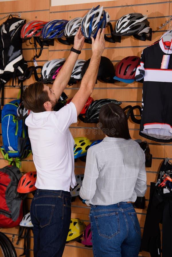 gerente novo que ajuda a escolher o capacete da bicicleta ao cliente fêmea imagens de stock