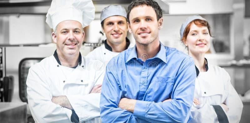 Gerente novo que levanta com alguns cozinheiros chefe foto de stock