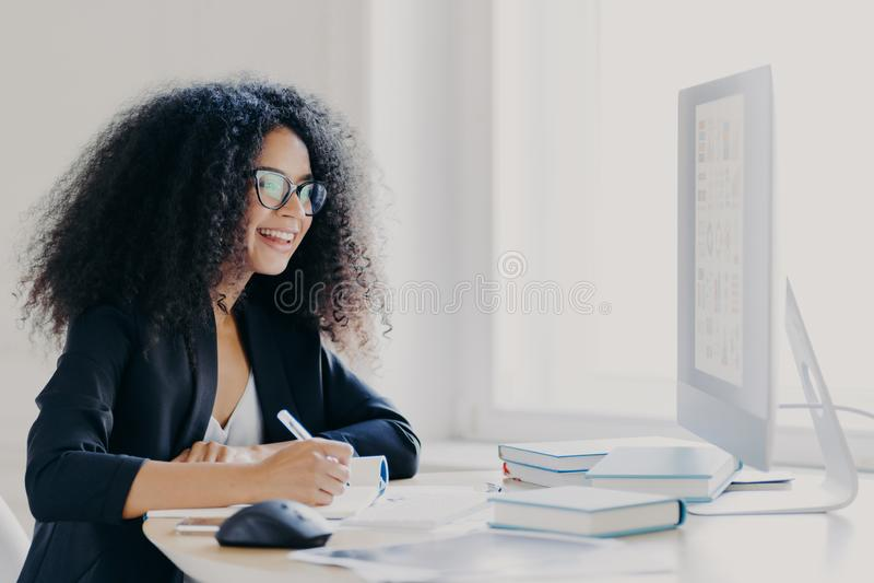 Gerente profissional de mulher cabeleira faz relatório, focado na tela, escreve informações, usa óculos e processo formal foto de stock