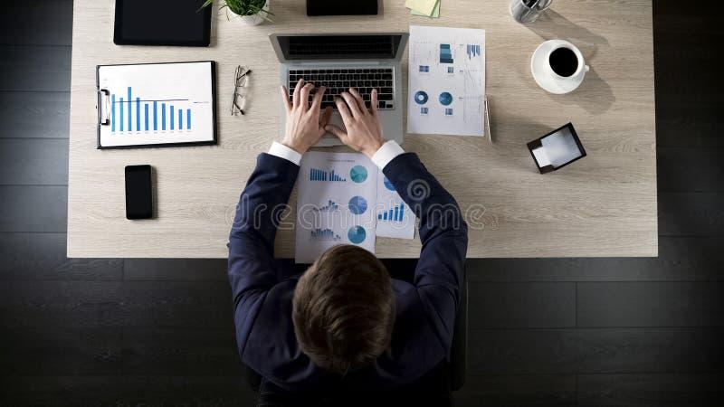 Gerente que compara estatísticas da empresa e que incorpora dados no portátil, vista superior fotos de stock