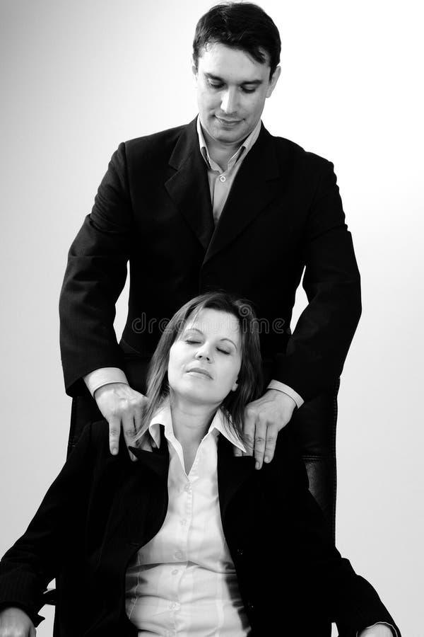 Gerente que faz massagens a mulher que senta-se na cadeira imagem de stock royalty free