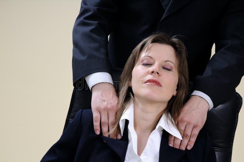 Gerente que faz massagens a mulher que senta-se na cadeira imagens de stock
