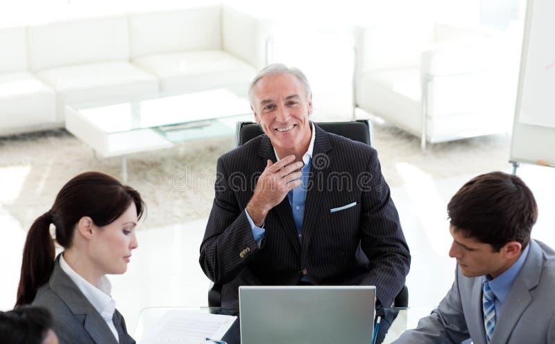 Gerente que sorri na câmera em uma reunião fotos de stock