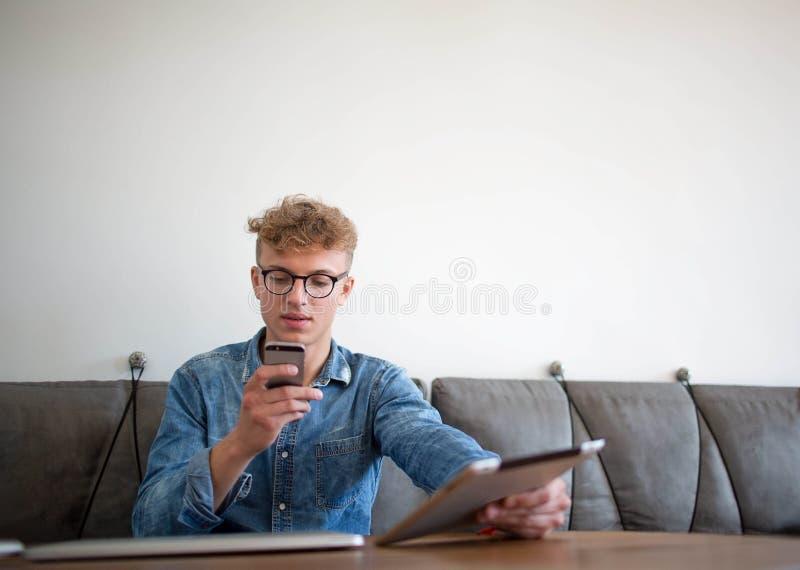 Gerente satisfeito masculino que verifica o email no telefone de pilha Indivíduo do moderno que conversa no telefone celular foto de stock