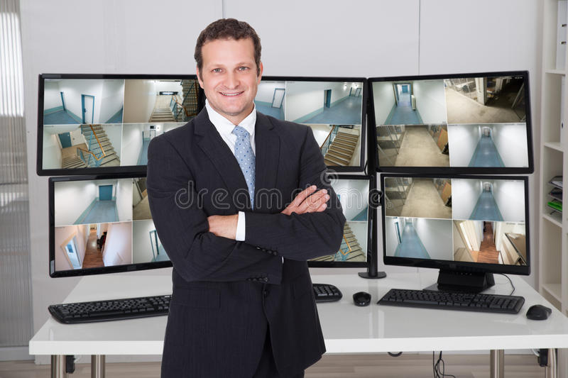 Gerente Standing Arms Crossed contra monitores no escritório foto de stock royalty free