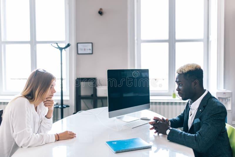 Gerentes afro-americanos e caucasianos que comunicam-se na tabela do escritório Homem negro que escuta com atenção ao colega que  imagem de stock