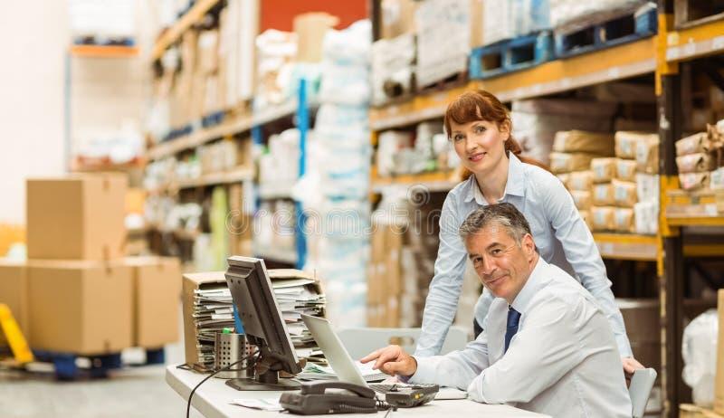 Gerentes do armazém que trabalham junto no portátil foto de stock