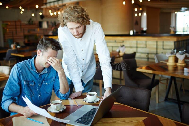 Gerentes esgotados que trabalham no café imagem de stock
