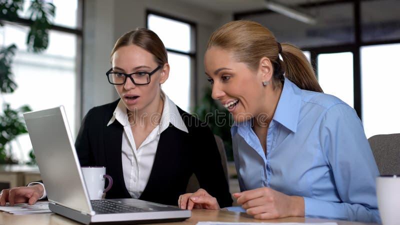 Gerentes fêmeas que leem grandes notícias no portátil, partida bem sucedida de júbilo fotos de stock