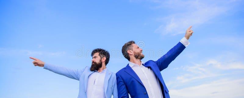 Gerentes formais do terno dos homens que apontam em sentidos opostos Curso em mudança Sentidos novos do negócio Negócio tornando- imagens de stock