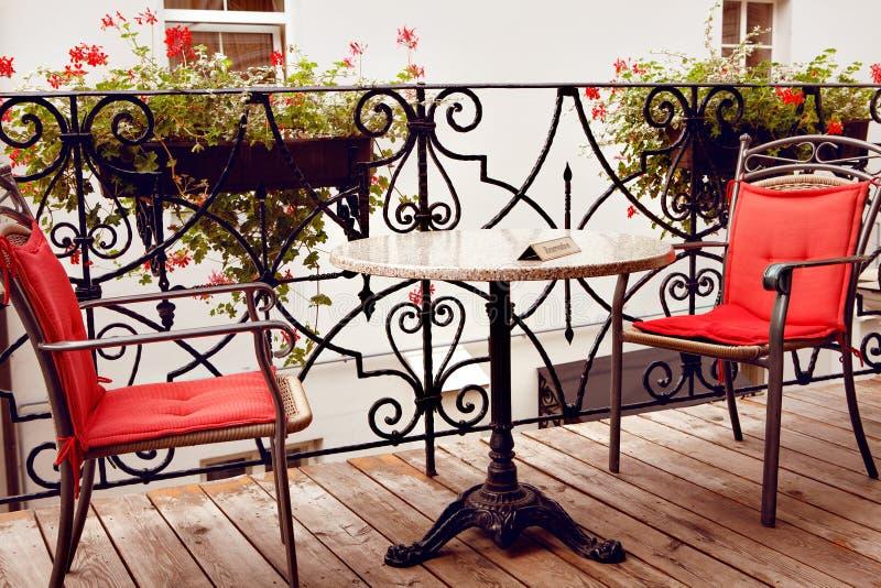 Gereserveerde lijst met rode stoelen Koffieterras in kleine Europese stad stock afbeelding