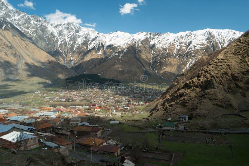 Gergeti en Stepantsminda-dorpen tussen bergen royalty-vrije stock afbeelding