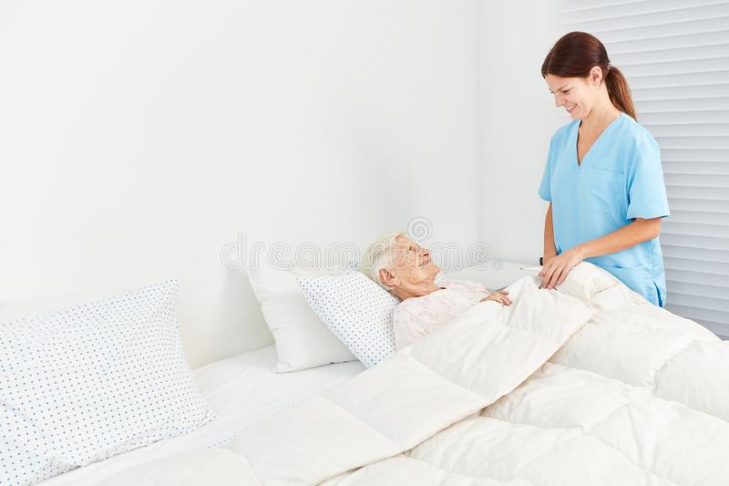 Geriatric care takes care of elderly woman in the hospice. Female carer or geriatric nurse takes care of the elderly at the hospice royalty free stock photography