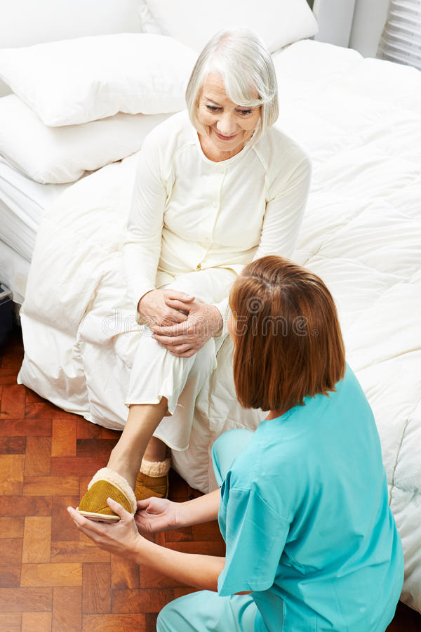 Geriatric caregiver helping old woman. Geriatric caregiver helping old women putting on her slippers in a nursing home stock image