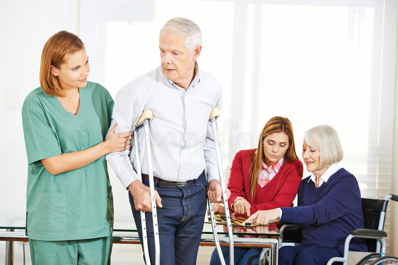 Geriatric caregiver with senior people. In nursing home stock photography