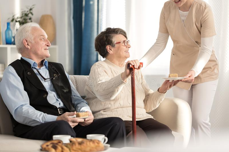 Geriatric couple with arthritis sitting. On a couch and being served a piece of cake while waiting for a doctor`s appointment at a luxury private clinic stock photo