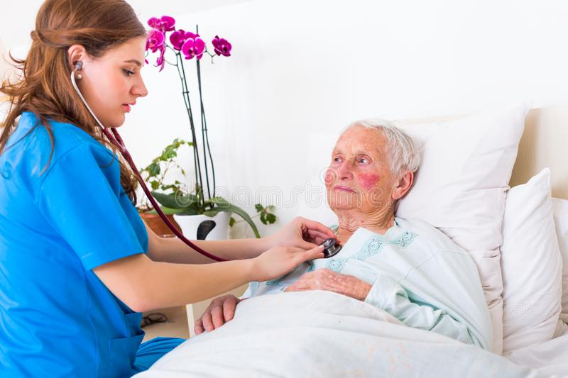 Geriatric examination. Happy elderly women assisted by geriatric doctor, examination in the nursing home stock photo