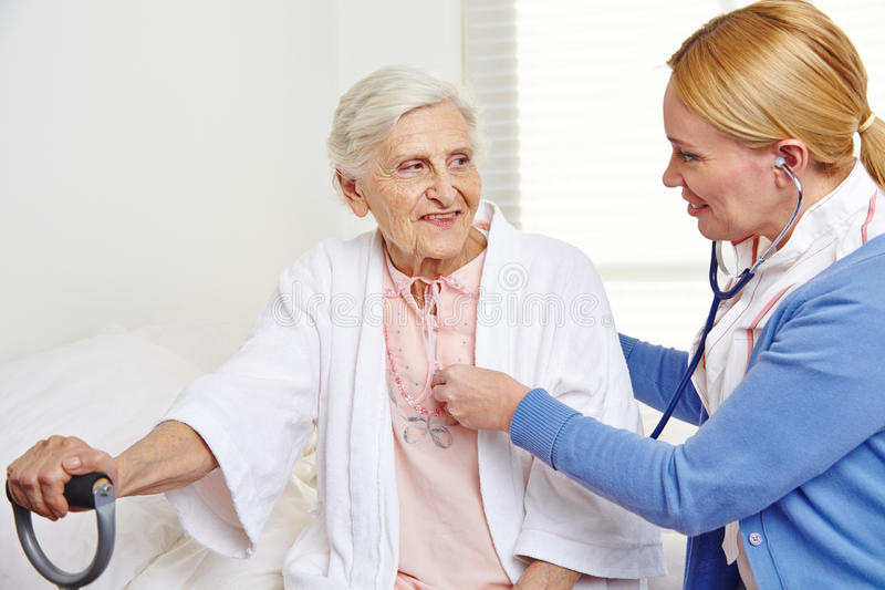 Geriatric nurse ausculting senior. Citizen women in nursing home royalty free stock photography