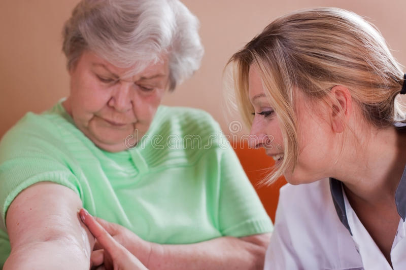 Geriatric nurse cares for elderly womans arm. Geriatric nurse makes home visits and supplies wounds royalty free stock image