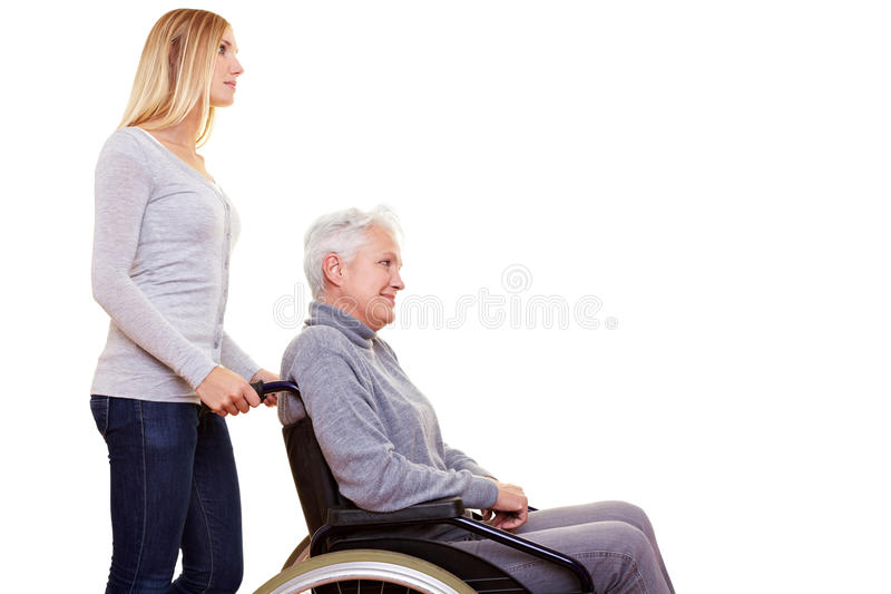 Geriatric nurse driving woman. Young geriatric nurse driving elderly woman in wheelchair stock image