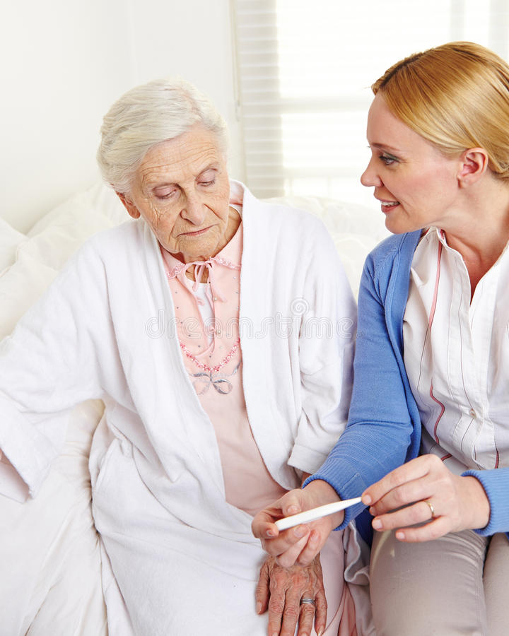 Geriatric nurse with fever. Thermometer and senior patient at home royalty free stock photography